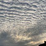 沈みゆく夕日と玄界灘上空の鰯雲